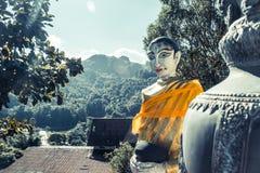 Le elemosine del ` s del monaco della tenuta della statua di Buddha lanciano a Wat Pilok Temple nel parco nazionale di Pha Phum d fotografia stock