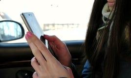 Le ` en gros plan s de femme remet causer son téléphone portable se reposant dans la voiture Vue de côté photographie stock