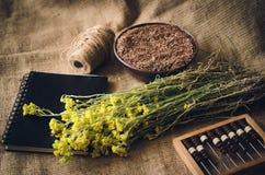 Le erbe ed i semi si trovano sulla tavola accanto al taccuino ed all'abaco di legno Stile rustico d'annata Fuoco molle fotografia stock
