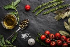 Le erbe si mescolano con i pomodori e l'olio d'oliva sulla tavola di pietra nera Fotografie Stock Libere da Diritti