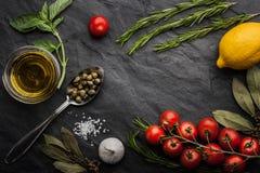 Le erbe si mescolano con i pomodori, il limone e l'olio d'oliva sulla tavola di pietra nera Immagine Stock
