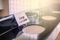 Le etichette identificano i rubinetti funzionanti male nel bagno Immagine Stock