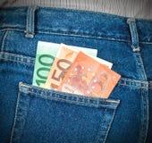 Le euro banconote che attaccano dai jeans posteriori intascano Immagini Stock