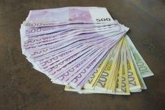 Le euro banconote dei contanti si sono sparse fuori sulla tavola Immagini Stock