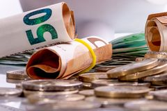 Le euro banconote hanno rotolato e le monete dell'euro nelle posizioni differenti fotografia stock libera da diritti