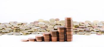 Le euro monete di valuta che costruiscono una scala e le monete dell'euro si sono sparse su un fondo bianco Fotografie Stock