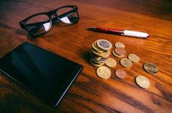 Le euro monete e biglietto dei soldi hanno messo a fuoco in vetri su una tavola di legno Finanza e concetto dell'ufficio Messo a  Fotografia Stock