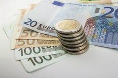Le euro monete e le banconote dei soldi impilate su a vicenda dentro differen Immagini Stock