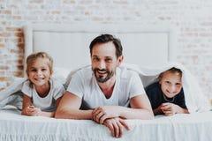 Le föräldern och två ungar som lägger på säng arkivfoton