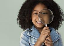 Le för förstoringsglas för liten flicka hållande Arkivfoto