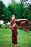 Le för stående av den härliga indiska flickan Ung indisk kvinnamodell med den röda smyckenuppsättningen royaltyfri bild