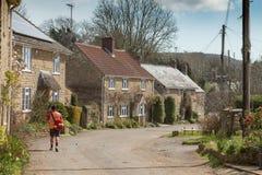 Le facteur fournit des lettres dans le village anglais Photographie stock libre de droits