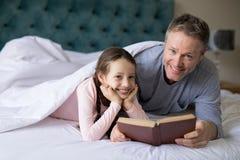 Le fader- och dotterläseboken på säng Royaltyfri Bild