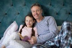 Le fader- och dotterläseboken på säng Arkivfoton