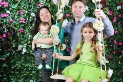 Le fadern, behandla som ett barn modern med och den lilla dottern på gunga Fotografering för Bildbyråer