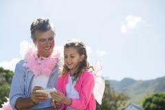 Le fadern och dottern i den felika dräkten som ser foto på mobiltelefonen Fotografering för Bildbyråer
