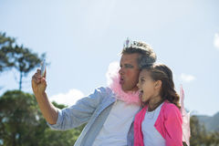 Le fadern och dottern i den felika dräkten som tar selfie på mobiltelefonen Arkivfoto