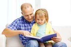 Le fadern och dottern med den hemmastadda boken arkivbilder