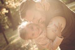Le fadern och hans liten flicka som in plying, parkera tillsammans royaltyfria bilder