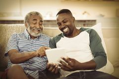 Le fadern och sonen som använder den digitala minnestavlan i vardagsrum arkivbild
