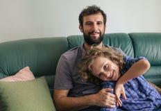 Le fadern och sonen som hemma sitter på deras soffa arkivbild