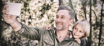Le fadern och sonen som tar selfie i skog arkivfoton