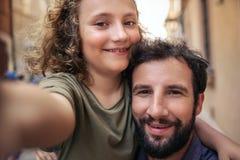 Le fadern och sonen som tar selfies på en stadsgata arkivfoton