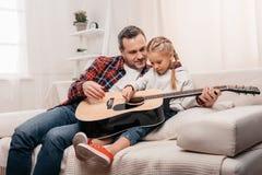 le fadern som undervisar gulligt litet spela för dotter som är akustiskt arkivbilder