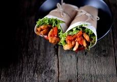 Le fajite con il pollo, pepe, cipolla in una salsa al pomodoro piccante, sono servito in una tortiglia Immagine Stock