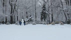 Le famiglie con un bambino fanno un pupazzo di neve stock footage
