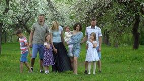Le famiglie, genitori con i bambini posano davanti alla macchina fotografica nel giardino di primavera video d archivio