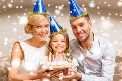 Le familjen i blåa hattar med kakan arkivbilder