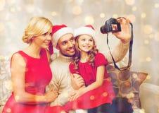 Le familjen i santa hjälpredahattar som tar bilden Arkivbild