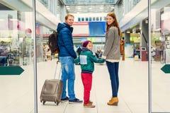 Le familjen med barnet på flygplatsen arkivbild