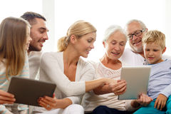 Le familjen med minnestavlaPC hemma royaltyfri bild
