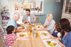 Le familjen med morföräldrar som diskuterar på att äta middag tabellen arkivbild