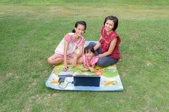 Le familjen som använder den utomhus- bärbara datorn arkivfoto