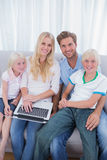 Le familjen som använder bärbara datorn i deras vardagsrum Arkivfoton