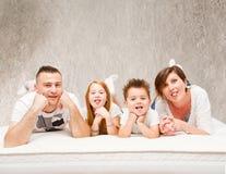 Le familjen som har gyckel som ligger på sängen Arkivfoton