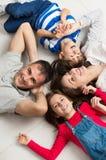 Le familjen som ligger på golv royaltyfria foton