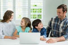 Le familjen som påverkar varandra med de, medan genom att använda bärbara datorn i vardagsrum Arkivfoton