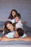 Le familjen som tillsammans spelar på sängen Fotografering för Bildbyråer