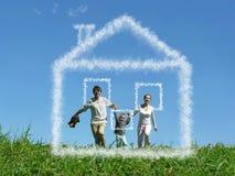 Le famille avec le garçon sur le pré et le rêve opacifient la maison Photos libres de droits