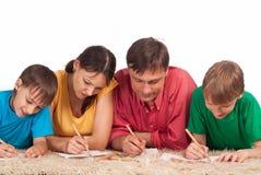 Le famille dessine sur le tapis Photos libres de droits