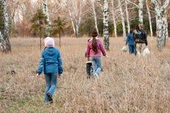 Le famille entre dans les bois d'automne Photo libre de droits