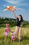 Le famille et les enfants heureux pilotent le cerf-volant. Photos libres de droits