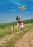 Le famille et les enfants heureux pilotent le cerf-volant. Photo libre de droits