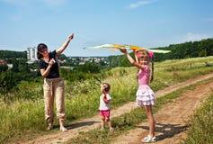 Le famille et les enfants heureux pilotent le cerf-volant. Photos stock
