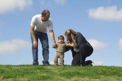 Le famille heureux effectuant le garçon sautent Photographie stock