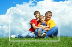 Le famille heureux s'asseyent sur l'herbe verte sous le ciel Photos stock